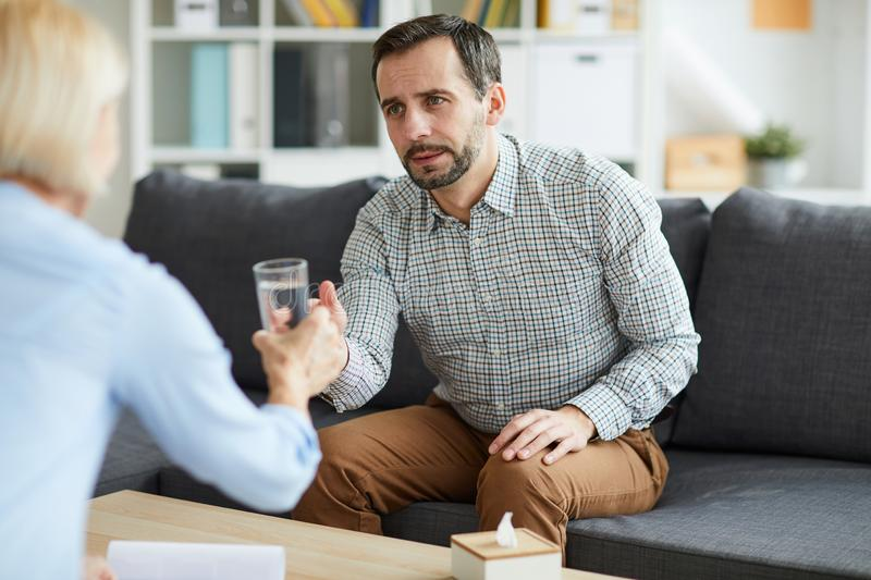 Taking glass of water. Young troubled men taking glass of water from his counselor while having discussion of his problems royalty free stock photos
