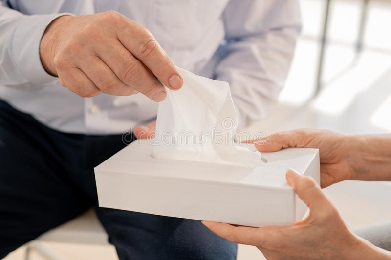 Taking handkerchief. Hand of senior man taking paper tissue from box being offered by groupmate or counselor royalty free stock photography