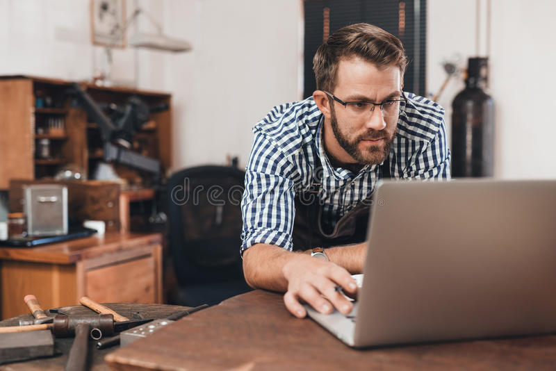 Taking his jewelry shop online stock photo