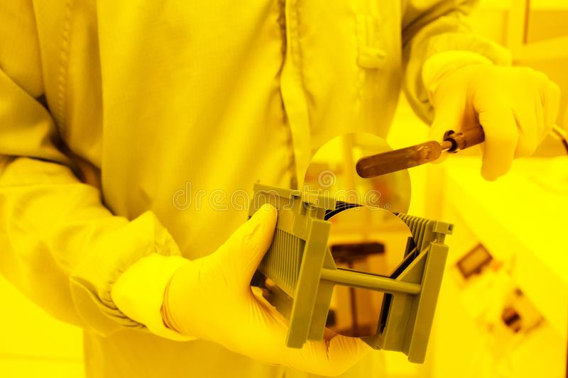 Taking a large wafer out of a tray with a vacuum tweezer. Wafer handling in a yellow room. Taking a large InP wafer out of a waferboat with a specialized vacuum stock photography