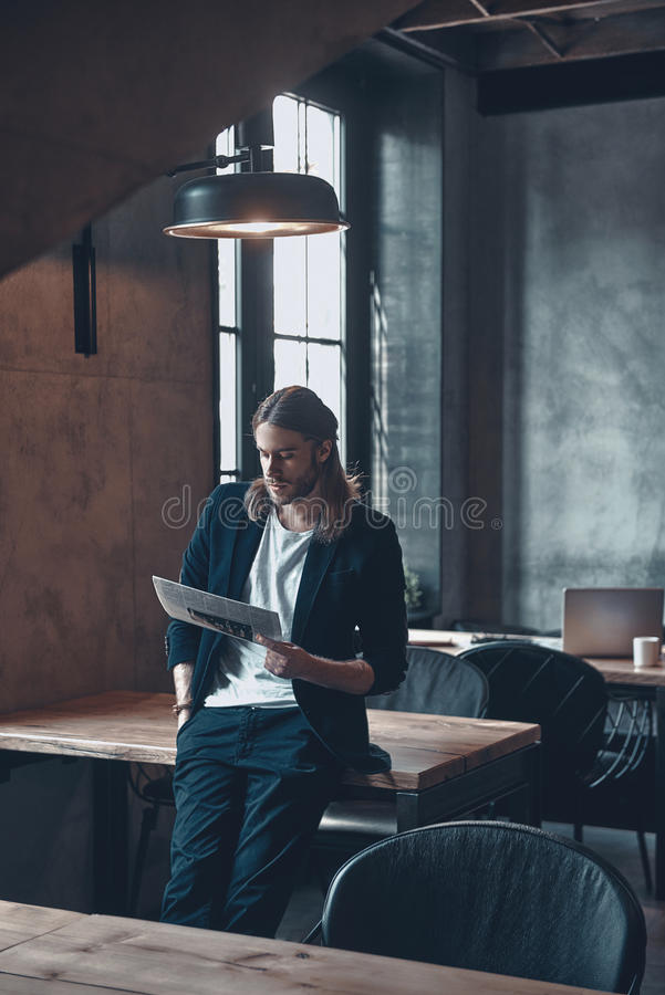 Taking little break. Serious young man in smart casual wear keeping hand in pocket and reading the newspaper while leaning on the office desk stock images