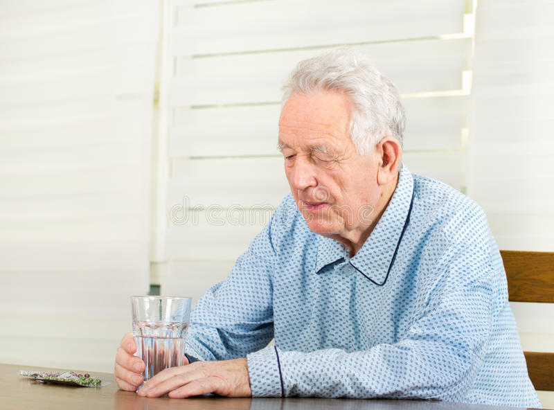 Taking medicals. Old depressed man in pajamas sitting at table with medicals and glass of water stock photography