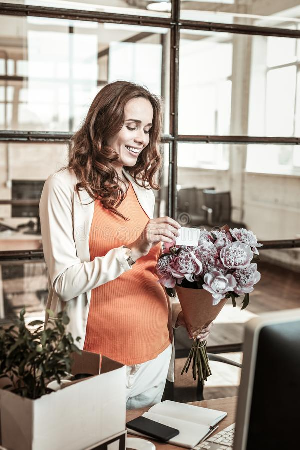 Contented attractive expecting woman being happy with flowers stock photos