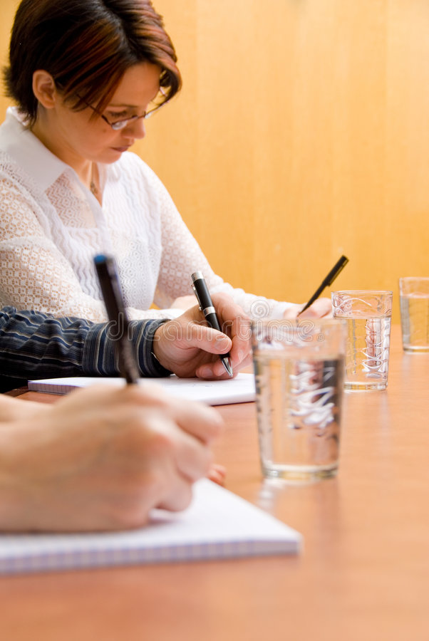 Taking notes. Business people writing in a meeting room royalty free stock photo