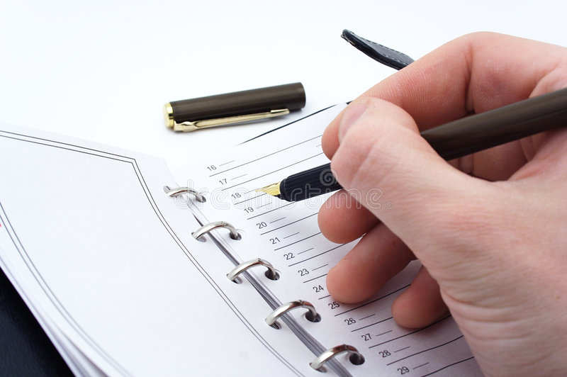 Taking notes. With brown pen stock photography