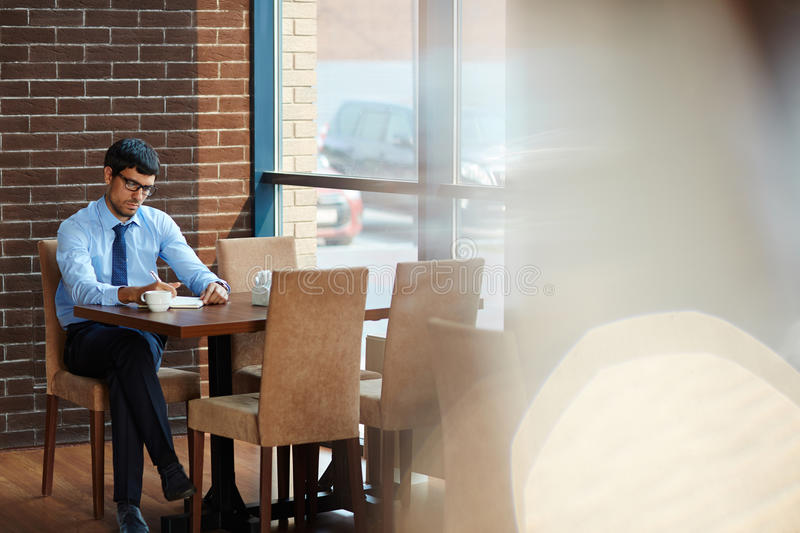Taking Notes During Coffee Break. Concentrated bearded entrepreneur taking necessary notes while sitting in cozy cafe with panoramic windows, full length stock photography