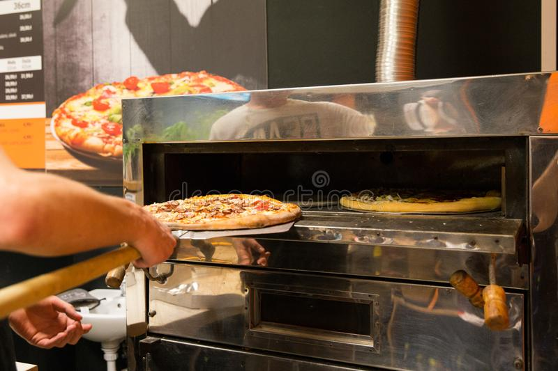 Pizza oven in pizza house. Taking out pizza from pizza oven. Great for commercial or social posts stock images