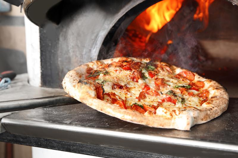 Taking out tasty pizza from oven in  kitchen stock image