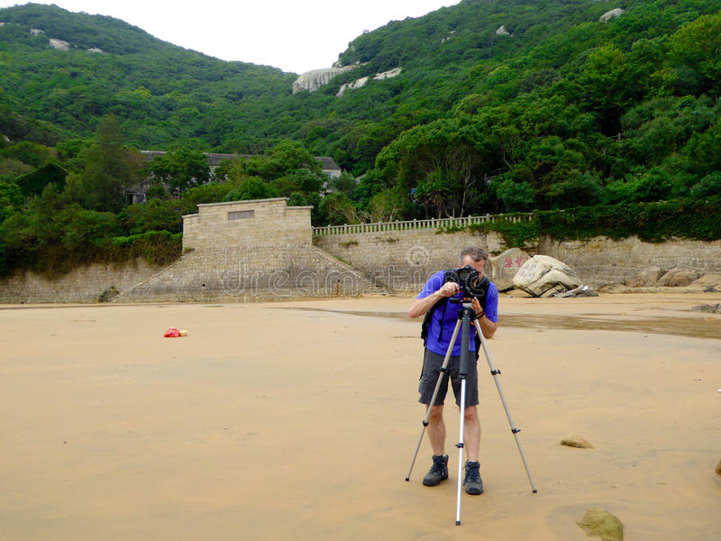 Taking photos on Thousand step sand beach. A man taking pictures on Thousand step sand beach with montains and trees background in Mount Putuo zhoushan city stock photos
