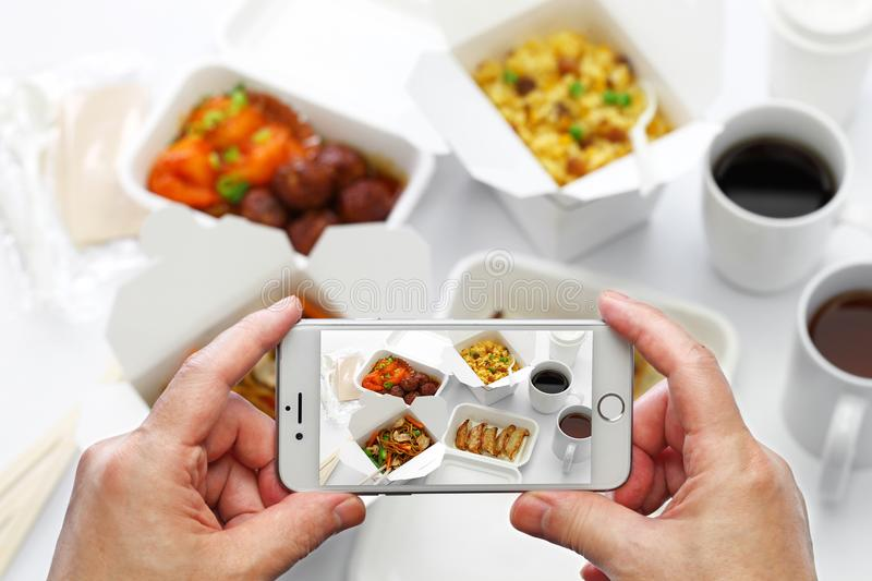 Taking a photo of chinese take out food with smartphone stock photo