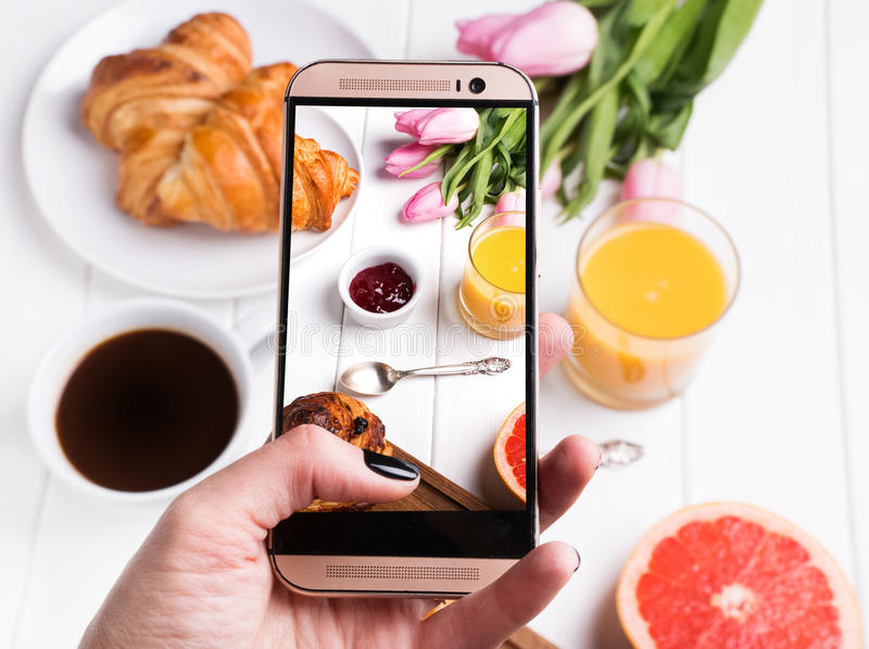 Taking photo of delicious breakfst with smartphone. Woman`s hand taking photo of delicious breakfst with smartphone close-up stock photos