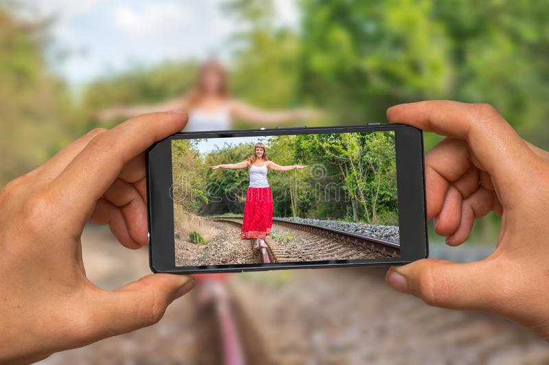 Taking photo of lady walking on railway with mobile phone royalty free stock photography