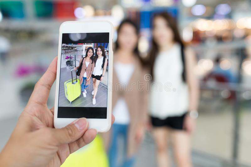 Taking photo on mobile phone in Hong Kong international airport. Beautiful young asian woman stock photography