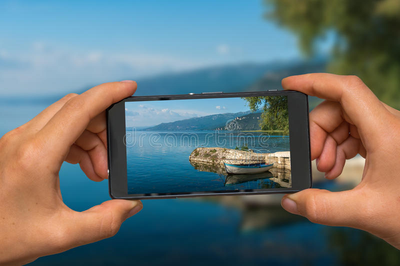 Taking photo of Ohrid lake in Macedonia with mobile phone. Woman hands with mobile cell phone to take a photo of Ohrid lake in Macedonia royalty free stock images