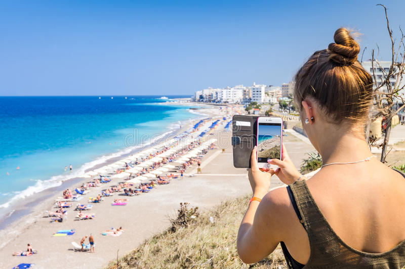 Taking photo tropical beach. Girl taking a landscape photo of beautiful tropical beach royalty free stock photography