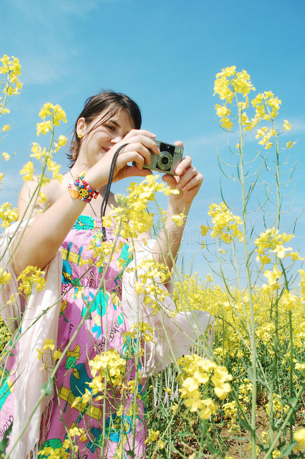 Taking photos. A beautiful girl taking photos of canola flowers royalty free stock image