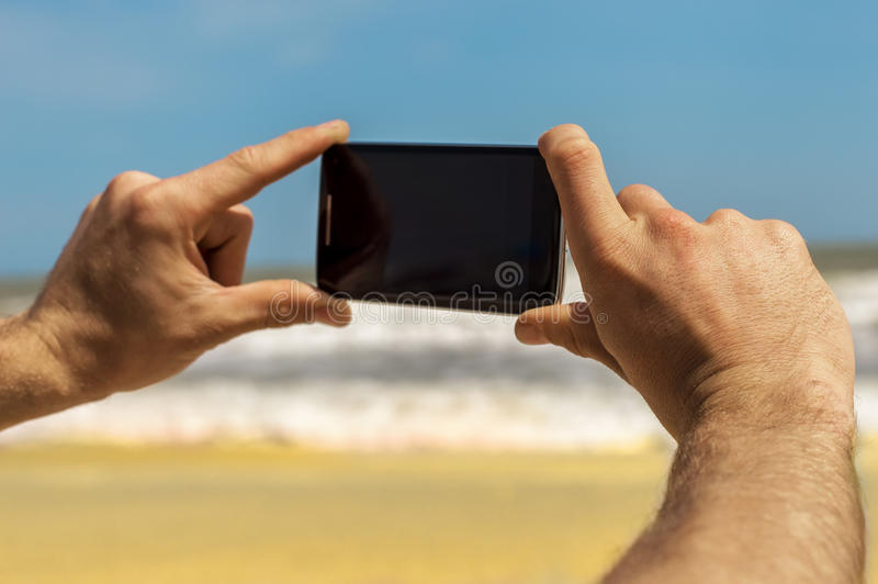 Taking photos on the phone at the sea royalty free stock photo