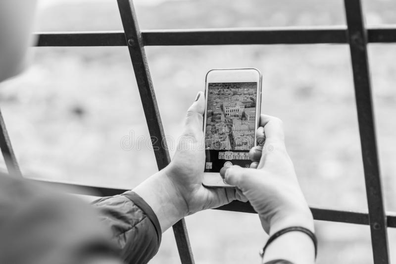 Taking picture of Bologna with cellphone from top of tower royalty free stock photography