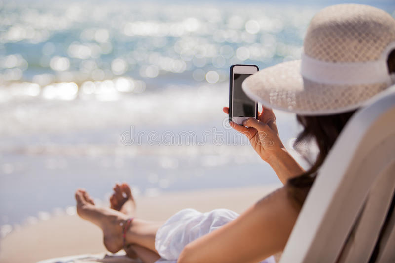 Taking a picture with a cell phone. Young woman sharing a picture of her vacations on the beach on a social network stock photos