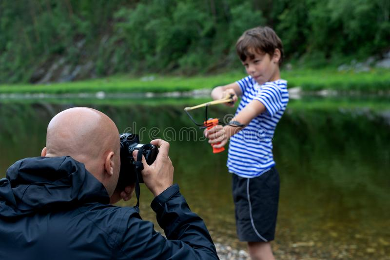 Taking a picture or a photo shoot in the open air. male photographer photographs a 9-year-old boy royalty free stock photo