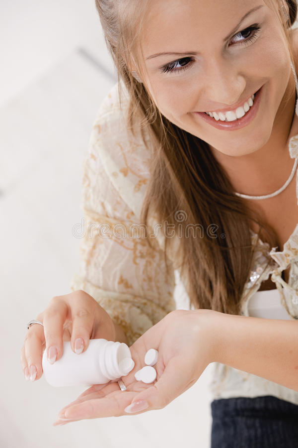 Taking pills from bottle. Portrait of young woman girl taking pills from bottle, smiling royalty free stock photo