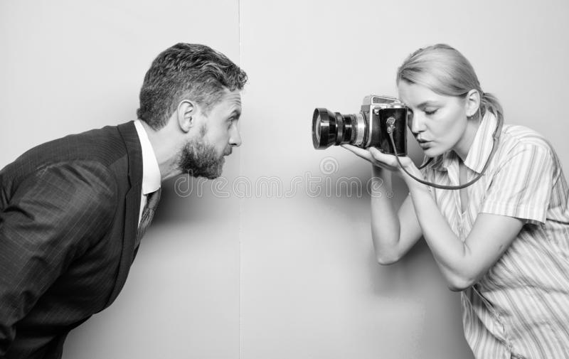 Taking a portrait. Businessman posing in front of female photographer. Fashion shooting in photo studio. Pretty woman stock photography