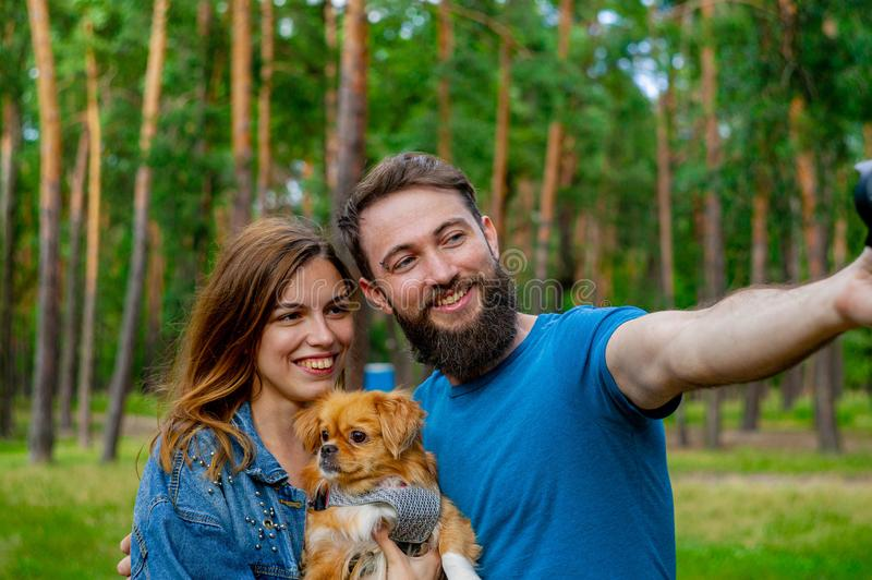 Taking selfie. Beautiful happy young-adult couple spending time on the grass with a white cute do stock images