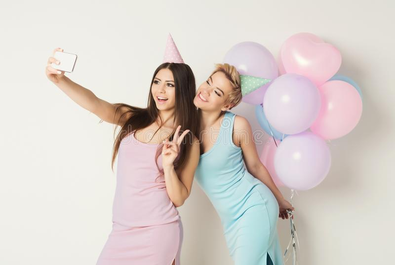 Two happy friends making selfie on smartphone at party stock photo