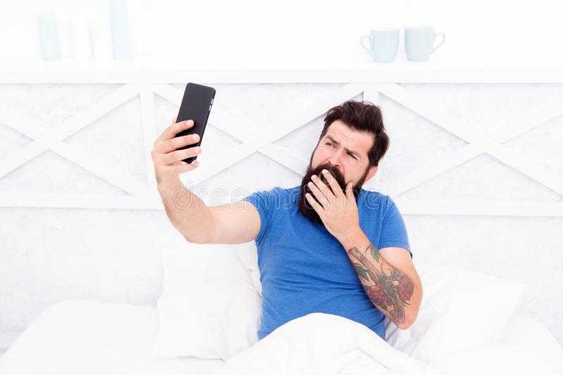 Taking selfie. Cellular communication. Modern guy talking on smartphone in bed. Modern technology for everyday life stock image