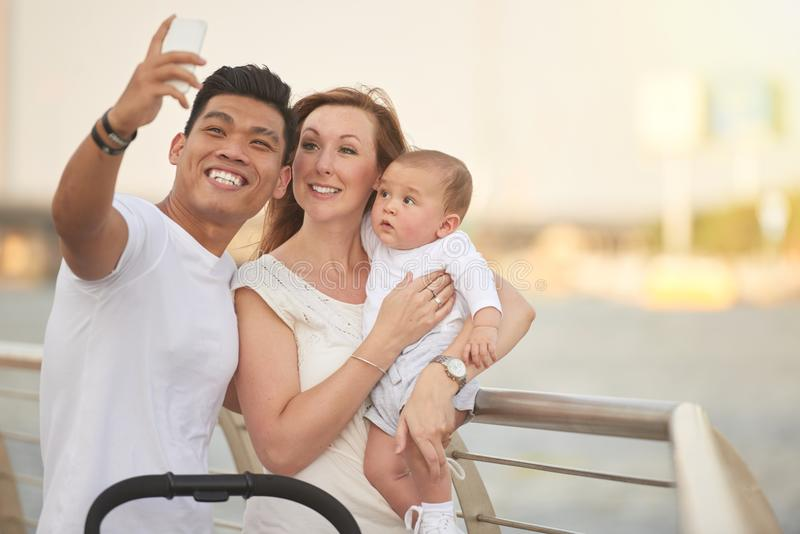 Taking Selfie with Loving Family. Mixed-race family of three taking selfie on smartphone while standing at riverwalk, cute baby looking at device with curiosity stock image