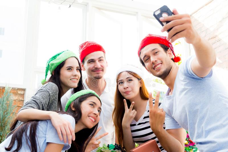 Taking a selfie portrait family or friends with smart phone on Merry Christmas and Happy New Year holiday. Smile men and women on xmas celebrating in winter royalty free stock photography
