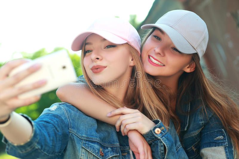 Taking selfie. Two girls friends or sisters have fun outdoor and taking selfie with smartphone royalty free stock photos