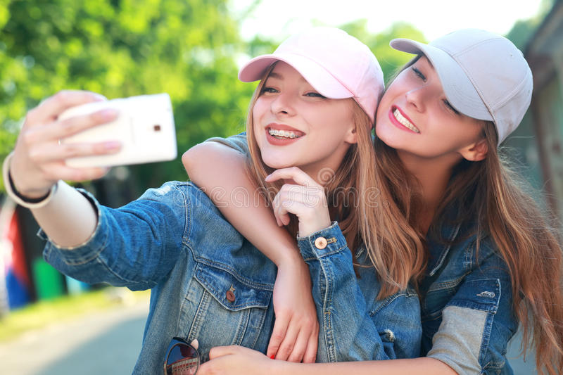 Taking selfie. Two girls friends or sisters have fun outdoor and taking selfie with smartphone stock photos
