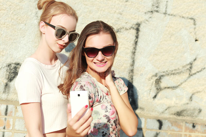 Taking selfie. Two girls friends or sisters have fun outdoor and taking selfie with smartphone royalty free stock images