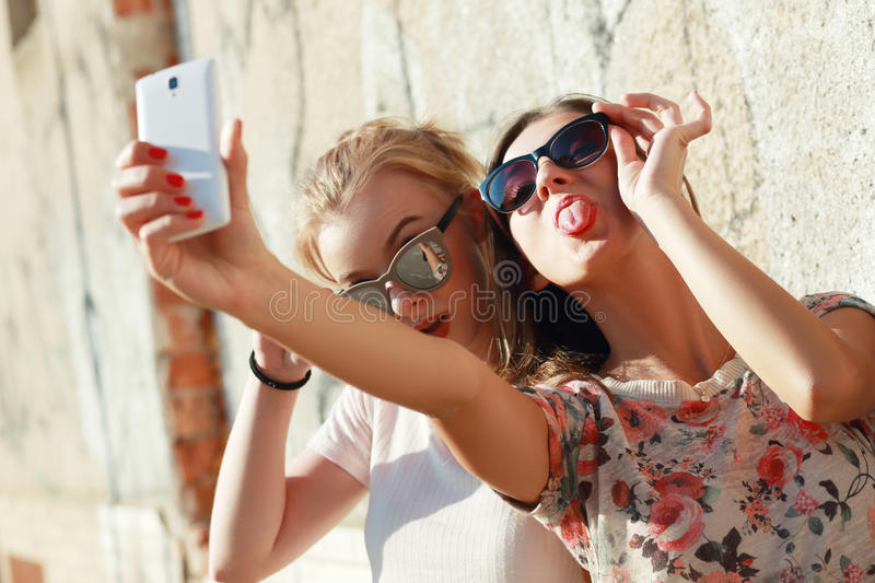 Taking selfie. Two girls friends or sisters have fun outdoor and taking selfie with smartphone stock photo
