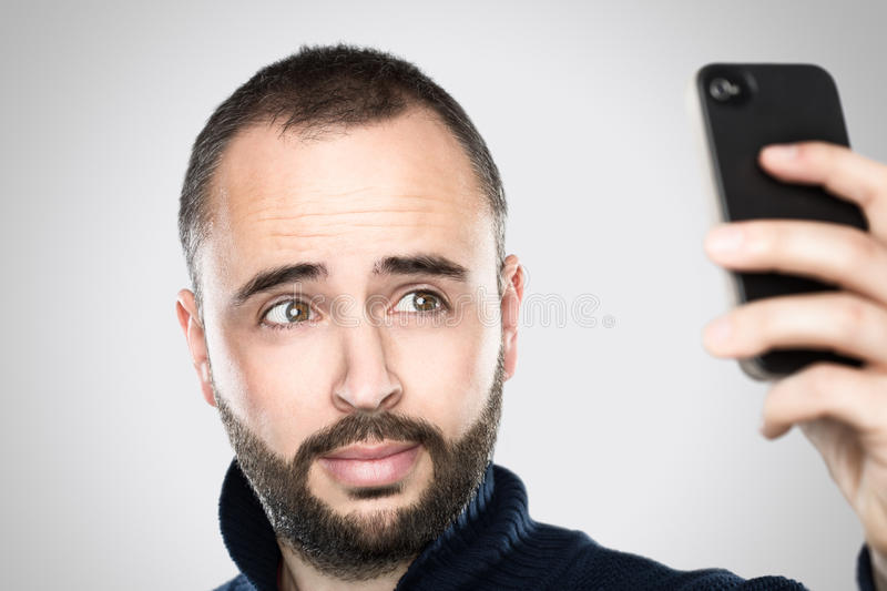 Taking a selfie. Young and handsome man is taking a selfie with his phone. Professional skin retouch royalty free stock photography