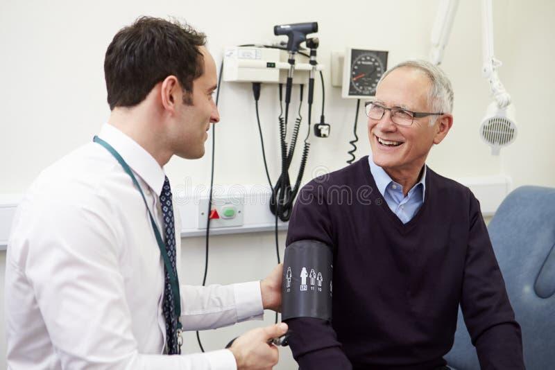 Taking Senior Patient医生的血压在医院 免版税图库摄影
