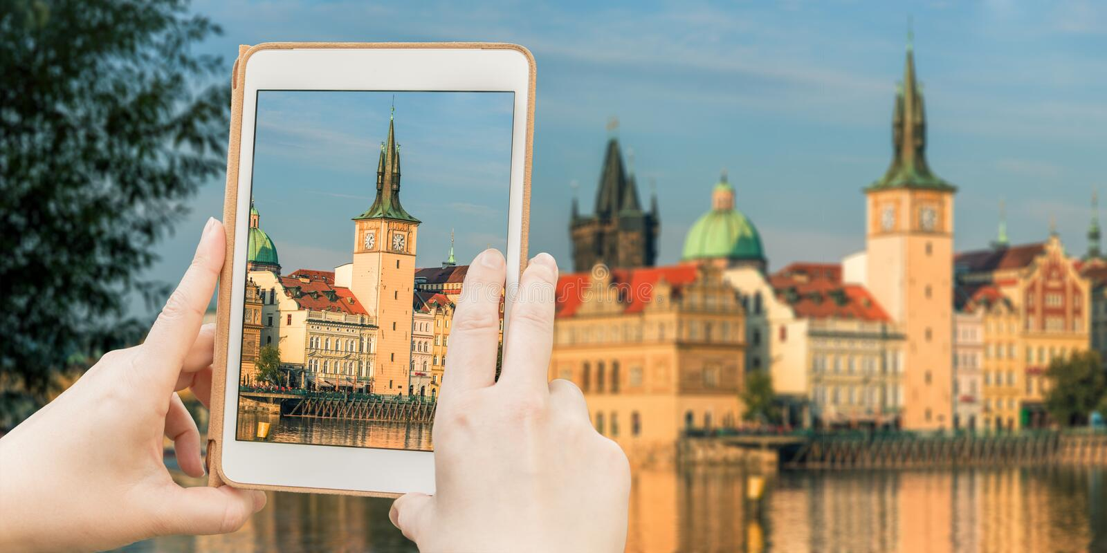 Taking shot of Panorama of Prague Old Town. Female tourist taking shot of beautiful panorama of Prague Old town and Charles bridge from the river Vltava with royalty free stock images
