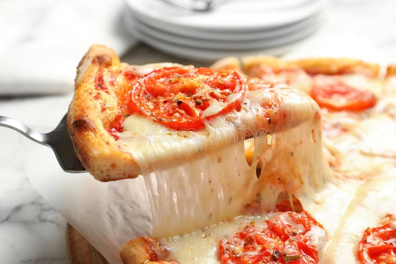 Taking slice of hot cheese pizza Margherita on table stock photo