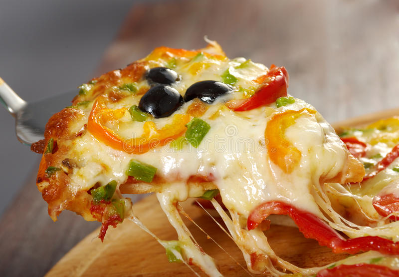 Taking slice of pizza,melted cheese dripping royalty free stock image
