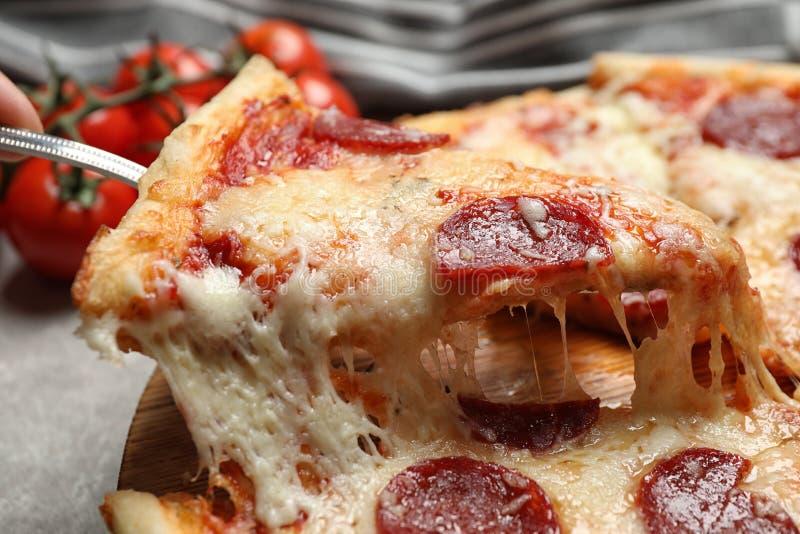 Taking slice of tasty pepperoni pizza on table, closeup stock photos