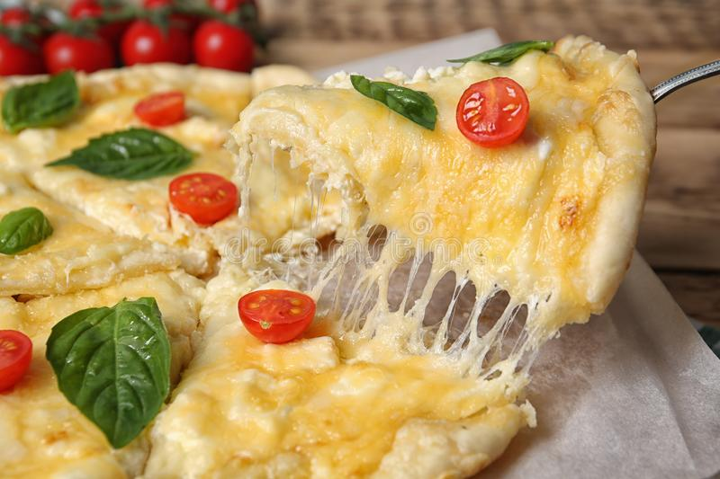 Taking tasty homemade pizza slice with melted cheese stock photography