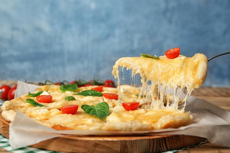 Taking tasty homemade pizza slice with melted cheese stock photo