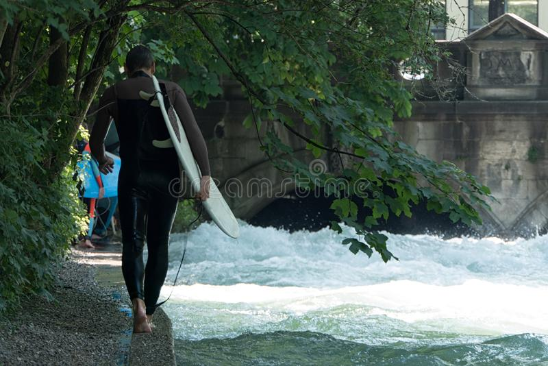 River Surfer of Munich, Germany Walking Along the Eisbach stock image