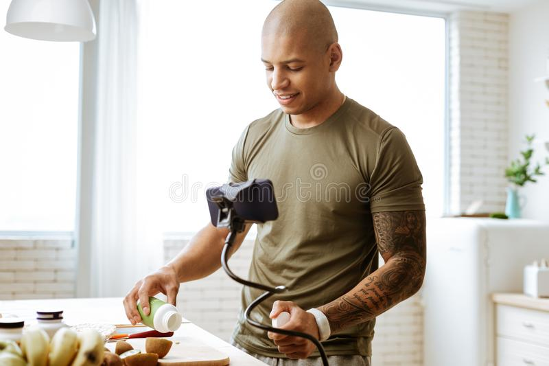Bald bodybuilder taking vitamins while cooking breakfast. Taking vitamins. Dark-skinned bald young bodybuilder taking vitamins while cooking breakfast stock photography