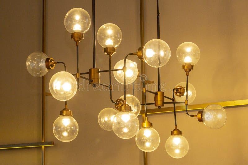 Takljuskrona från variation av lampor modern design, vind, ovanlig lampa royaltyfria foton