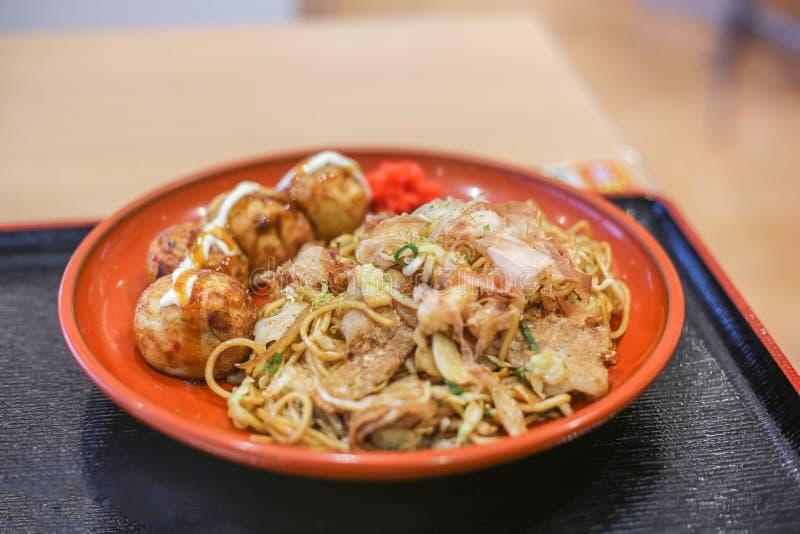 Takoyaki, bläckfiskbollar och yakisoba, japansk stekt nudel, i en platta arkivbilder