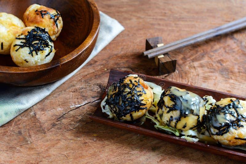 Takoyaki op houten lijst met eetstokjes stock afbeeldingen