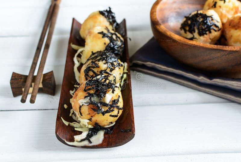 Takoyaki op houten lijst met eetstokjes stock afbeelding
