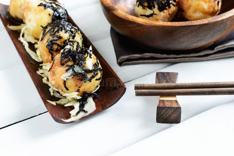 Takoyaki op houten lijst met eetstokjes stock fotografie